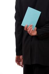 Blauer Brief hinter einem männlichen Rücken
