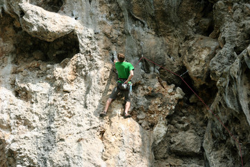 Rock climber climbing up a cliff.