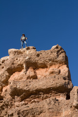 The tourist stands on the brink of a rock