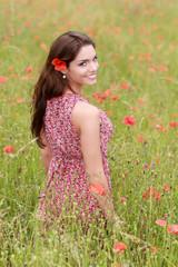 Jeune femme en robe fleurie dans un champ de coquelicot