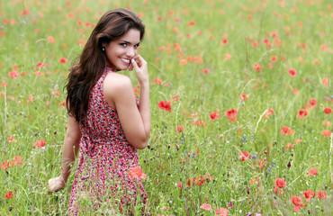 Jeune femme avec une robe fleurie dans un champ de coquelicot