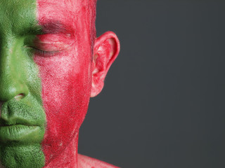 Man face painted flag of Portugal, closed eyes