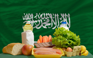 basic food groceries in front of saudi arabia national flag