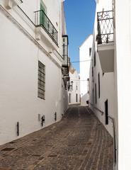 Calle estrecha de fachadas blancas