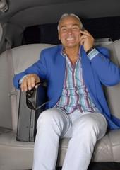 Hombre de negocios al teléfono en un auto.