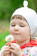 Funny child holding white dandelion
