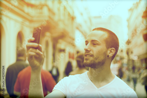 Man Take Photo With Mobile Phone On Street