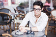 attractive man wearing glasses standing at a terrace