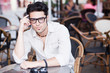attractive man wearing glasses standing at a terrace looking coo