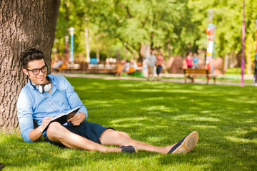 handsome man writing something and relaxing on the grass in the