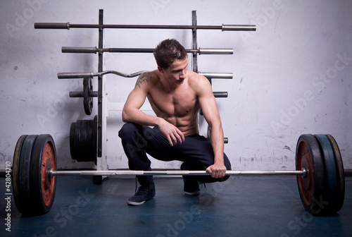 An athlete is preparing to lift a heavy dumbbell