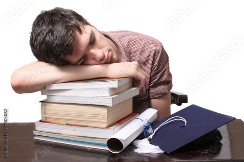 Graduate sleeping on books