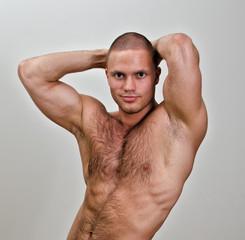 Muscular bodybuilder torso. On grey background.
