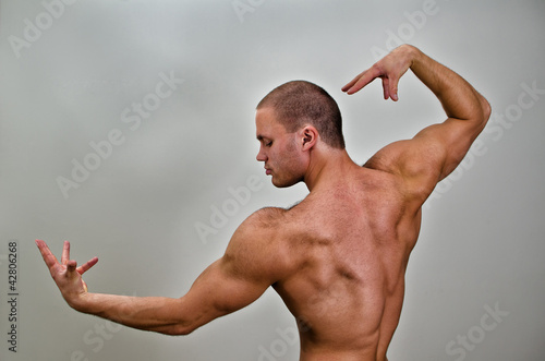 Muscular bodybuilder posing. On grey background.