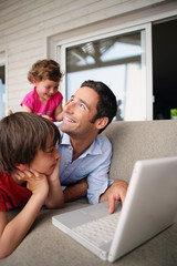 Father and children laughing at with a laptop