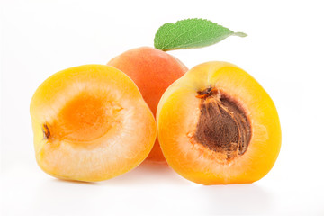Apricot fruits and slices with green leaves, isolated on white
