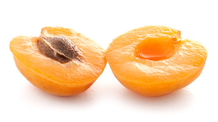 Apricot slices with green leaves, isolated on white background