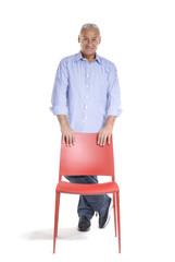 Señor de pie sujetando una silla roja.