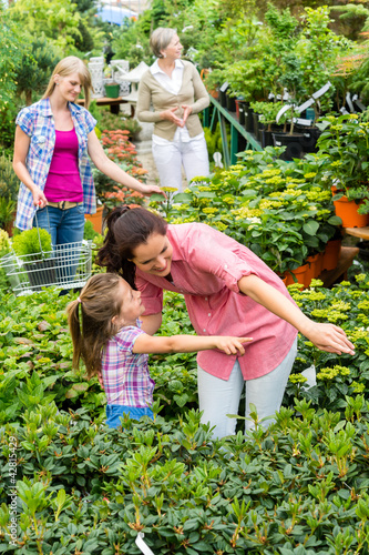 Mother daughter choosing flowers in garden center