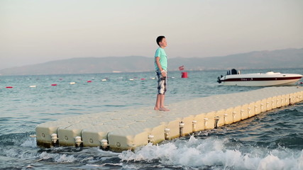 Young boy standing on platform floating on the water