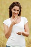 Jeune femme mangeant une barre de céréales dans un champ de blé