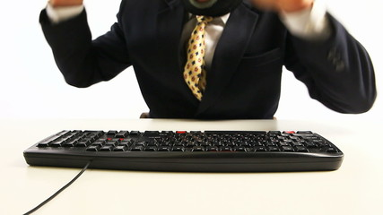 guy in official suit and balaclava beating the keyboard