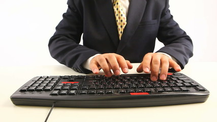 man in official suit typing on keyboard