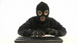 guy in balaclava and black gloves typing something in anger