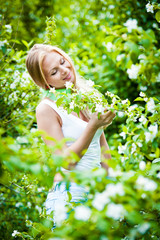 Attractive blonde girl in the garden on a sunny day.