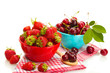 Ripe strawberries and cherry berries in bowls isolated on white