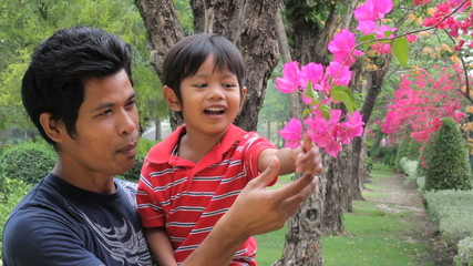 Father And Son Looking At Flowers Together