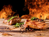 Fototapety Grilled beef steaks with flames on background