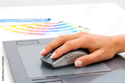 Female hand using mouse on digital tablet.