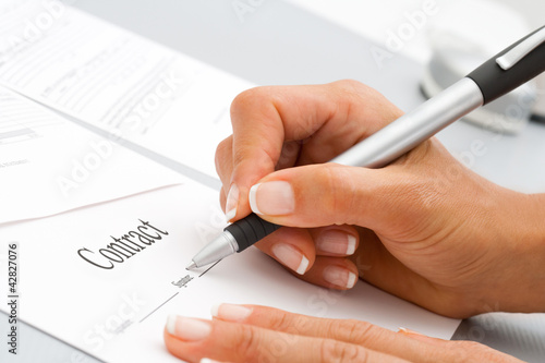 Macro close up of hand signing contract.