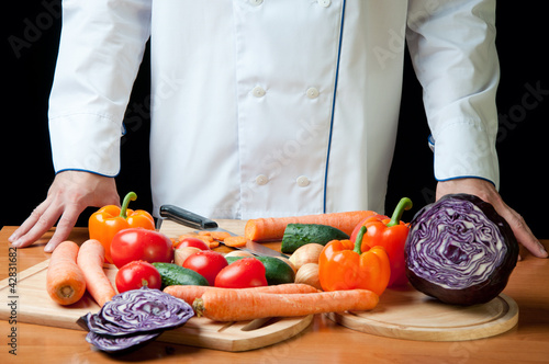 Chef standing by the kitchen table with variety of vegetables