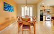 Orange dining room with hardwood floor and kitchen.