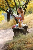 Young beautiful woman reading a book. Near it is the cat