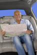 Hombre turista viajando en un auto sosteniendo un mapa.
