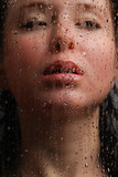 Naked girl in a wet glass on a black background