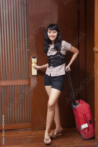 Young woman opening a hotel room