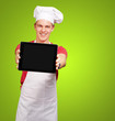portrait of young cook man showing a digital tablet over green b