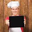 portrait of young cook man showing a digital tablet against a wo