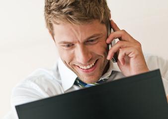 Junger Mann mit Handy und Laptop, Business, erfolgreich