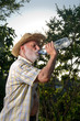 a farmer man drinks water from bottle