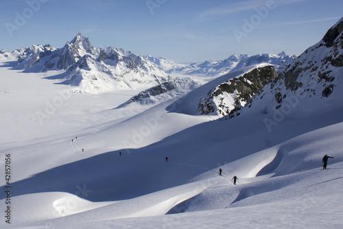 Papiers peints Pôle Montée à ski sur pente crevassée et paysage glaciaire infini.