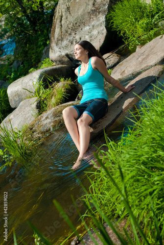 Young beautiful woman resting on river bank