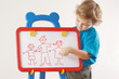Little cute boy shows his family painted on a whiteboard