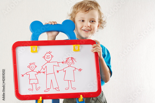Little smiling cute boy shows his family painted on a whiteboard