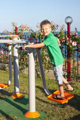 Boy is engaged on exercise machines, in the open air