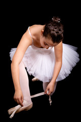 Ballerina dancer tiding up her shoe laces on black background